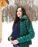 Den härliga gravida kvinnan i vinter beklär utomhus Arkivfoton