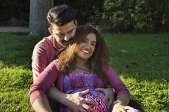 Den härliga gravida kvinnan och hennes make i parkerar royaltyfri fotografi