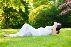 Den härliga gravida kvinnan parkerar på våren arkivfoto