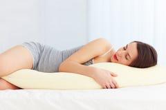Den härliga gravida kvinnan sover bekvämt med den understödjande kudden för magen Royaltyfri Fotografi