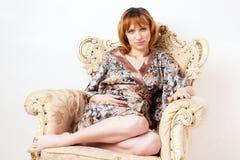 Den härliga gravida unga kvinnan i en placera Arkivbild