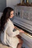 Den härliga gulliga flickan i vitt värme hemmastatt spela för omslag på gammalt piano Royaltyfria Foton