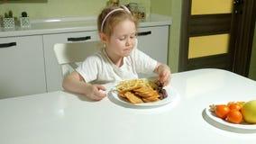 Den härliga gulliga lilla flickan vägrar frukt, väljer kakor, choklad, chiper arkivfilmer