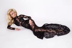 Den härliga högväxta slanka blondinen med den iklädda fantastiska kroppen en elegant klänning snör åt klänningen Arkivbild