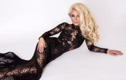 Den härliga högväxta slanka blondinen med den iklädda fantastiska kroppen en elegant klänning snör åt klänningen Royaltyfri Foto