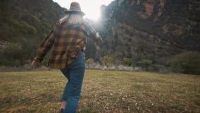 Den härliga handelsresanden för den unga kvinnan kör fritt över fältet i natur bland bergen Kastar en hatt in i luften arkivfilmer