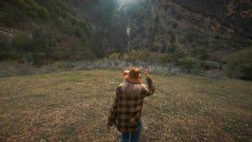 Den härliga handelsresanden för den unga kvinnan kör fritt över fältet i natur bland bergen Kastar en hatt in i luften lager videofilmer