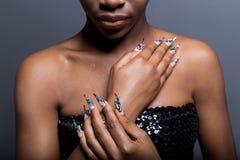 Den härliga handen av flickan med det mörka hudkneget av akryl spikar med spikar ovanligt fotmoy Arkivfoton