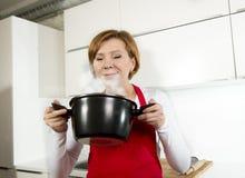 Den härliga hem- kockkvinnan på kökinnehavskeden och matlagning lägger in arkivfoto