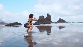 Den härliga idrotts- flickan i sportig kläder på stranden av havet utför squats Sund livsstil Kondition arkivfilmer