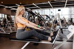 Den härliga idrotts- flickan med iklätt långt blont hår en sportswear gör sportövningar med utrustning på arkivbilder