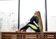 Den härliga idrotts- flickan med mycket långt blont hår sitter på träfönsterbrädan bredvid de panorama- fönstren in royaltyfri fotografi