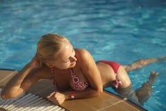 Den härliga innegrejen och den sexiga blonda flickan i bikini poserar i simbassäng arkivfoto