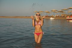 Den härliga innegrejen och den sexiga sportiga blonda flickan i bikini har en rolig tid i havet Royaltyfri Foto