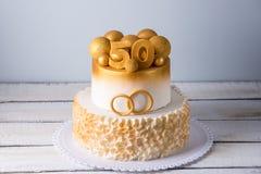Den härliga kakan för den 50th årsdagen av bröllopet dekorerade med guld- bollar och cirklar Begrepp av festliga efterrätter Royaltyfria Bilder