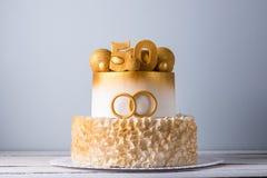 Den härliga kakan för den 50th årsdagen av bröllopet dekorerade med guld- bollar och cirklar Begrepp av festliga efterrätter Royaltyfri Bild