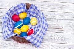 Den härliga korgen med färgat färgade fega ägg på färgrikt rutigt tyg och på vit träbakgrund, dekorativt kopieringsutrymme arkivbild