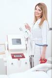 Den härliga kosmetologen på hennes arbetsplats ska applicera tillvägagångssätt av laser-epilationen eller att lyfta för rf Royaltyfria Bilder