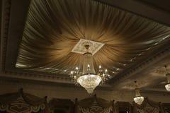 Den härliga kristallkronan smyckar taket av restaurangen royaltyfri foto