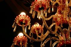 Den härliga kristallkronan som göras av rött exponeringsglas, inställs från taket royaltyfri fotografi