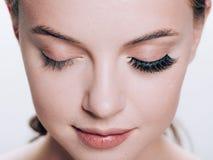 Den härliga kvinnaframsidan med ögonfrans piskar hud för skönhet för förlängningen före och efter sund som naturlig makeup stängd royaltyfri fotografi