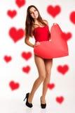 Den härliga kvinnan är hållande stor pappers- röd hjärta Royaltyfri Bild