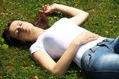 Den härliga kvinnan är ligga och vila i gräset Royaltyfri Bild