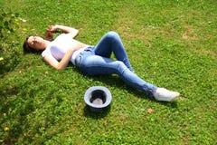 Den härliga kvinnan är ligga och vila i gräset Fotografering för Bildbyråer