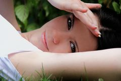 Den härliga kvinnan är ligga och vila i gräset Royaltyfri Fotografi