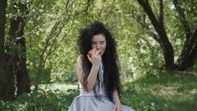 Den härliga kvinnan äter nytt äpplesammanträde i sommarträdgård lager videofilmer