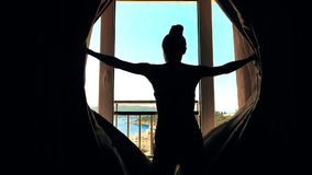 Den härliga kvinnan öppnar gardiner av seaviewfönstret lager videofilmer