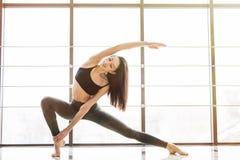 Den härliga kvinnan öva yogaasanaen Anjaneyasana i studio royaltyfria foton
