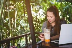 Den härliga kvinnan använde smartphonen, bärbara datorn och med is te på tabellen av Royaltyfria Foton