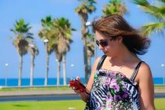 Den härliga kvinnan använder en smartphone Royaltyfri Fotografi