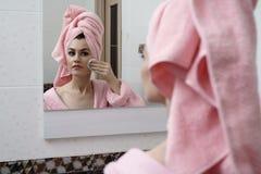 Den härliga kvinnan att bry sig för hud i spegel Royaltyfria Foton