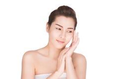 Den härliga kvinnan att bry sig för hudframsidan, den attraktiva asiatiska kvinnan som trycker på hennes framsida Royaltyfri Foto