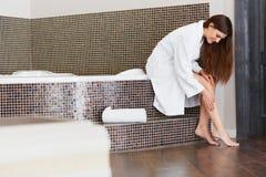 Den härliga kvinnan att bry sig om ben efter bad lång kvinna för ben Arkivbilder