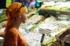 Den härliga kvinnan beskådar produkter Fotografering för Bildbyråer