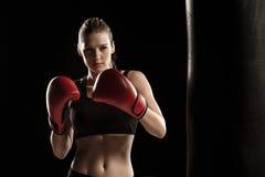 Den härliga kvinnan boxas på svart bakgrund royaltyfria bilder
