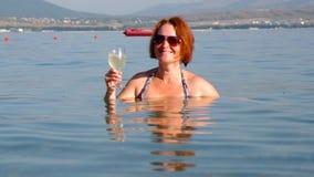 Den härliga kvinnan dricker exponeringsglas av Royaltyfri Fotografi