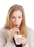 Den härliga kvinnan dricker från en kopp med sugrör. arkivfoton