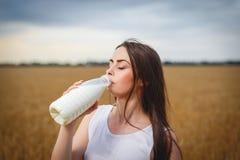 Den härliga kvinnan dricker mjölkar i bygd Arkivbilder