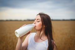Den härliga kvinnan dricker mjölkar i bygd Arkivfoton