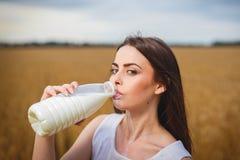 Den härliga kvinnan dricker mjölkar i bygd Royaltyfria Bilder