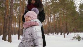 Den härliga kvinnan går i vinterskog med den lilla dottern lager videofilmer