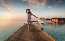 Den härliga kvinnan går ner en träbrygga på Maldiverna Arkivfoton