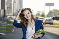 Den härliga kvinnan går till och med gatorna som lyssnar till musik på hörlurar med en bukett arkivfoton