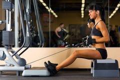 Den härliga kvinnan gör övningar på idrottshallen Royaltyfria Bilder