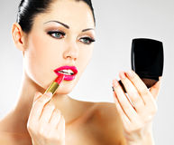 Härlig kvinna som applicerar rosa läppstift på kanter royaltyfri bild