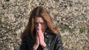 Den härliga kvinnan har plötsligt allergical tecken, når han har luktat blomstrad trädultrarapid stock video